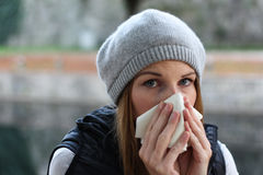 Woman blowing into tissue. Sick woman with a cold blowing into tissue Stock Image