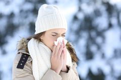 Woman blowing in a tissue in a cold snowy winter. Woman blowing in a tissue in a cold winter with a snowy mountain in the background royalty free stock photo