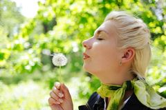Woman blowing to dandelion flower Royalty Free Stock Images