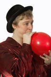 Woman blowing up a balloon. Short hair blond caucasian middle-age woman wearing a black party hat blowing up a red balloon stock image