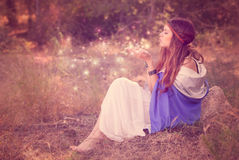 Woman blowing wishes in forest. fairy or elf. Woman blowing magic wishes in forest. fairy or elf Stock Images