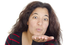 Woman and a blown kiss. Young woman with dark hair and a blown kiss royalty free stock photos