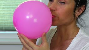 Woman blows the balloon close up stock footage