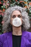 Woman blows bubbles with chewing gum. Good looking woman elegantly dressed and wide open eyes blows bubbles with chewing gum stock photos