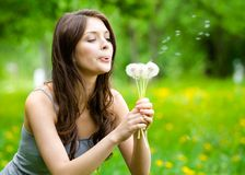 Woman blows dandelions in the park Stock Photography