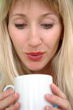 The woman blows in a mug Royalty Free Stock Photo