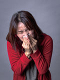Woman blows nose hard. Stock Photos