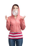 Woman blows out bubble gum. Woman in sweatshirt blows out pink bubble gum, isolated on white royalty free stock image