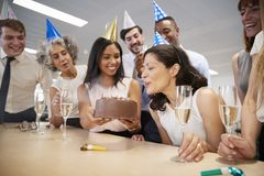 Woman blows out candles on birthday cake in office stock images