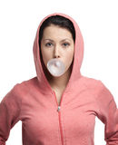 Woman blows out pink bubble gum. Lady in sweatshirt blows out pink bubble gum, isolated on white stock image