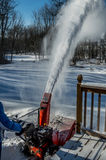 Woman Blows Snow after Storm. A woman blows snow into the back yard with a snow blower Royalty Free Stock Image