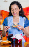 Woman with a blue apron putting some blackberry jam on a toast.  Stock Photos