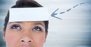 Woman with blue arrow pointing to card on head against blurry blue wood panel. Digital composite of Woman with blue arrow pointing to card on head against blurry Stock Photography