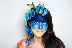 Woman blue art face. Bright blue butterflies seating on woman head, hair. Oriental beauty girl professional makeup. Portrait of a beautiful lady dark side of Royalty Free Stock Images