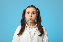 Woman show cheeks. Woman on blue background show cheeks looking at camera Royalty Free Stock Images