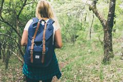 Woman in Blue Backpack Standing Facing Forest Stock Image