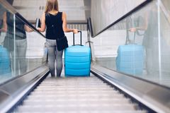 Woman with blue baggage suitcase on escalator stock images