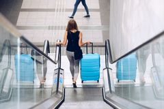 Woman with blue baggage suitcase on escalator royalty free stock photography