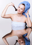 Woman in blue bath towel on head with makeup brush Royalty Free Stock Image