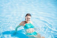 Woman in blue bathing suit in pool. body in water. Vocation and relaxing royalty free stock image