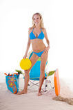 Woman In Blue Bikini On Beach. Young blond fashion model wearing a azure blue bikini standing on the beach with a Frisbee Royalty Free Stock Photography