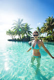 Woman in blue bikini inside tropical infinity pool Royalty Free Stock Images