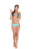 Woman in blue bikini pointing to copy space Stock Image