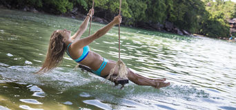 Woman in blue bikini on rope swings. Adult Caucasian woman in blue bikini swinging on a rope swings by the beach Royalty Free Stock Photography