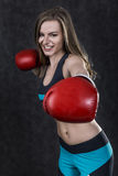 Woman in blue and black making a punch Royalty Free Stock Photos