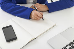 Woman in blue blazer is taking notes at a table Royalty Free Stock Photography