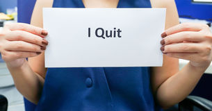 Woman with blue blouse quit from job. Woman hold a banner of I quit to her boss Stock Photography