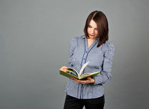 Woman in blue blouse standing and reading her green notes Royalty Free Stock Photo