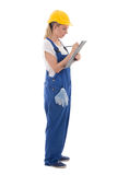 Woman in blue builder uniform writing something on clipboard iso Stock Image