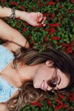 Woman in Blue Chambray Spaghetti Strap Dress Wearing Sunglasses With Red Flower Background royalty free stock images