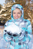 Woman in blue checkered jacket with snow in hands in winter fore Royalty Free Stock Photography