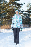 Woman in blue checkered jacket walking in winter forest Stock Photos