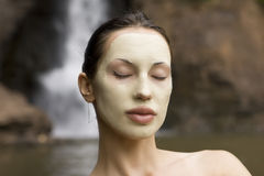 Woman with blue clay facial mask in beauty spa. Royalty Free Stock Photography