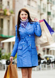 Woman in blue cloak with purchases at street Royalty Free Stock Photography