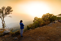 Woman in blue coat looking sunset at cliff in winter Stock Images