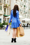 Woman in blue coat with purchases Royalty Free Stock Image