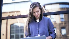 Woman in blue coat typing on laptop outside. Beautiful young woman in a blue coat is typing on her laptop in the street. Locked down real time close up shot stock footage