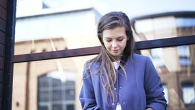 Woman in blue coat typing on laptop outside, handheld. Beautiful young woman in a blue coat is typing on her laptop in the street. Handheld real time close up stock footage