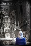 Woman in a blue coat and white veil praying - selective color stock images
