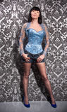 Woman in blue corset and stockings posing against wall Stock Photography