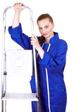 Woman in blue coveralls with metal ladder Royalty Free Stock Photos