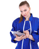 Woman in blue coveralls  writing on clipboard Stock Photo