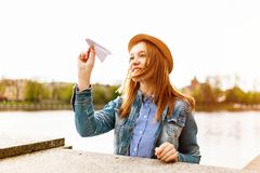 Woman in Blue Denim Button-up Jacket and Brown Hat About to Fly a Paper Plane Beside a Body of Water royalty free stock photos