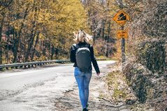 Woman in Blue Denim Fitted Jeans and Wearing Grey Backpack Walking on Gray Asphalt Road Near Road Signage and Trees at Daytime Royalty Free Stock Images