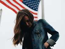 Woman in Blue Denim Jacket Behind U.s.a Flag during Daytime Royalty Free Stock Images