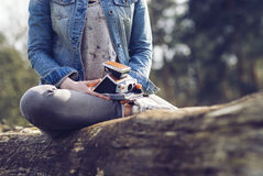 Woman in a Blue Denim Jacket and Gray Denim Skinny Jeans Sitting on a Tree Branch Royalty Free Stock Images